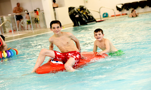 Boys playing on floats at Newark Sports and Fitness Centre pool