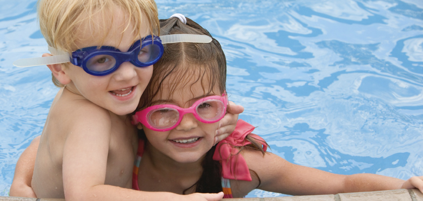 Girl and boy having fun in a swimmming pool